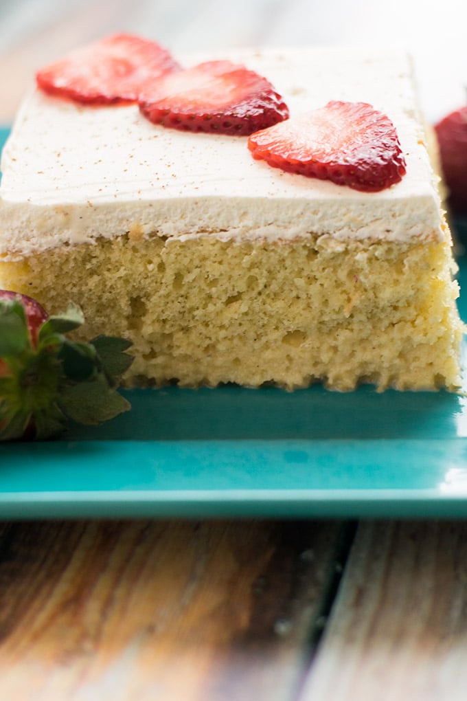 pastel de tres leches with sliced strawberries on top on a blue plate