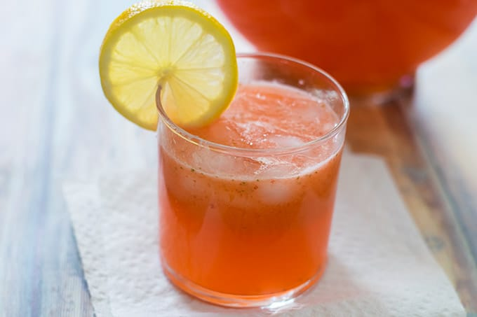 strawberry lemonade in a clear glass with a lemon slice