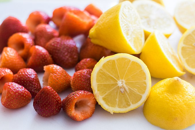 hulled strawberries and halved lemons on a white cutting board