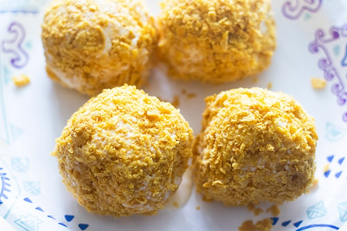 four ice cream balls rolled in crushed corn flakes