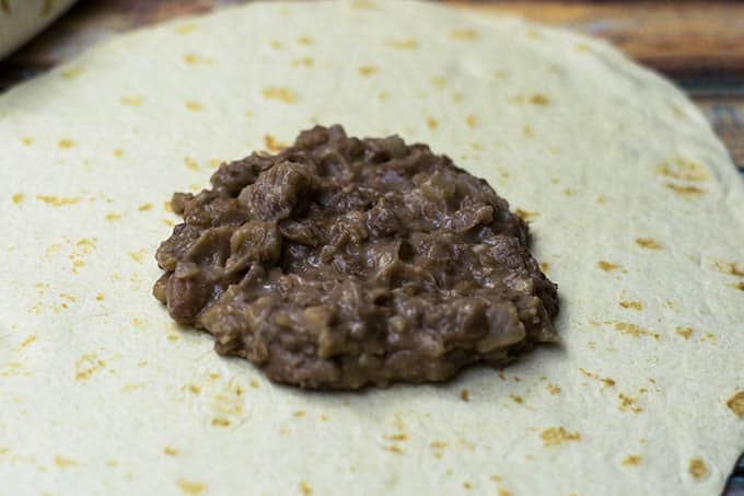 refried pinto beans on tortilla