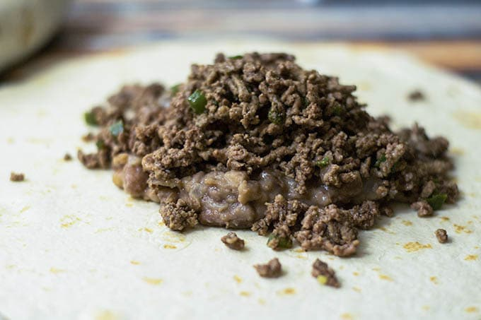 refried beans and ground beef on a flour tortilla