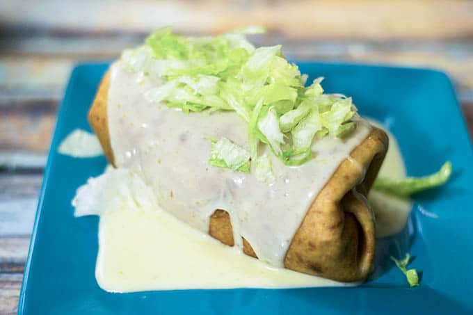 chimichanga covered in queso and garnished with lettuce