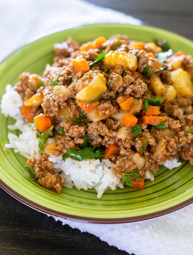 mexican picadillo over white rice on a green plate.
