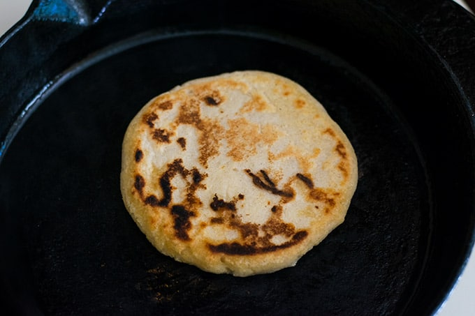 pupusa on a cast iron skillet.