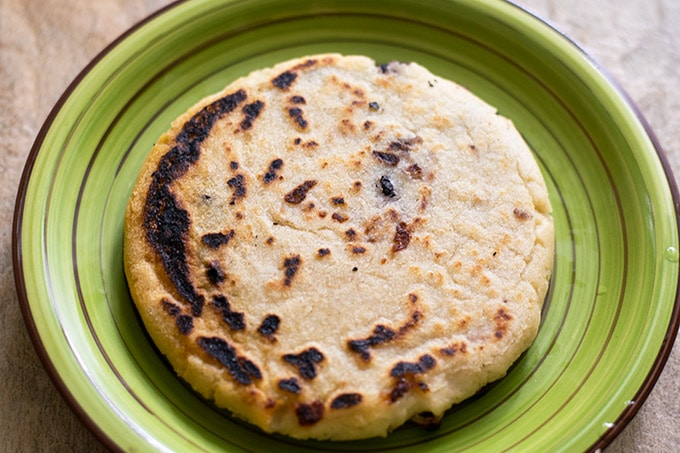 bean and cheese pupusa on a green plate