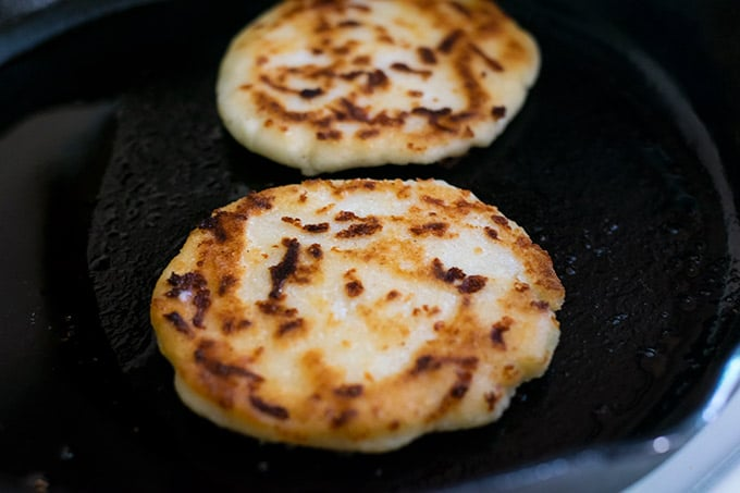 cooking cheese arepas on a skillet