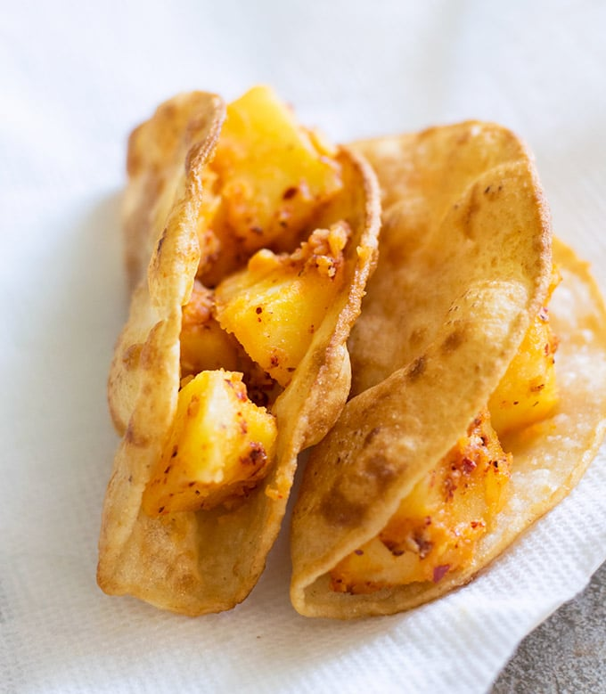 two hard shell tacos filled with spicy potatoes