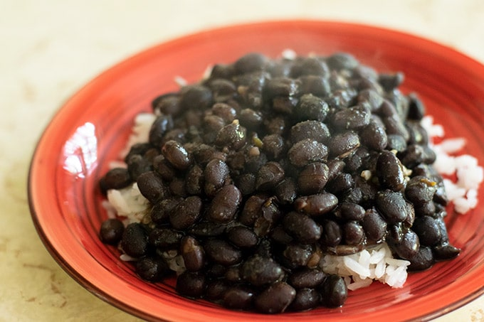 black beans served over white rice on a red plate