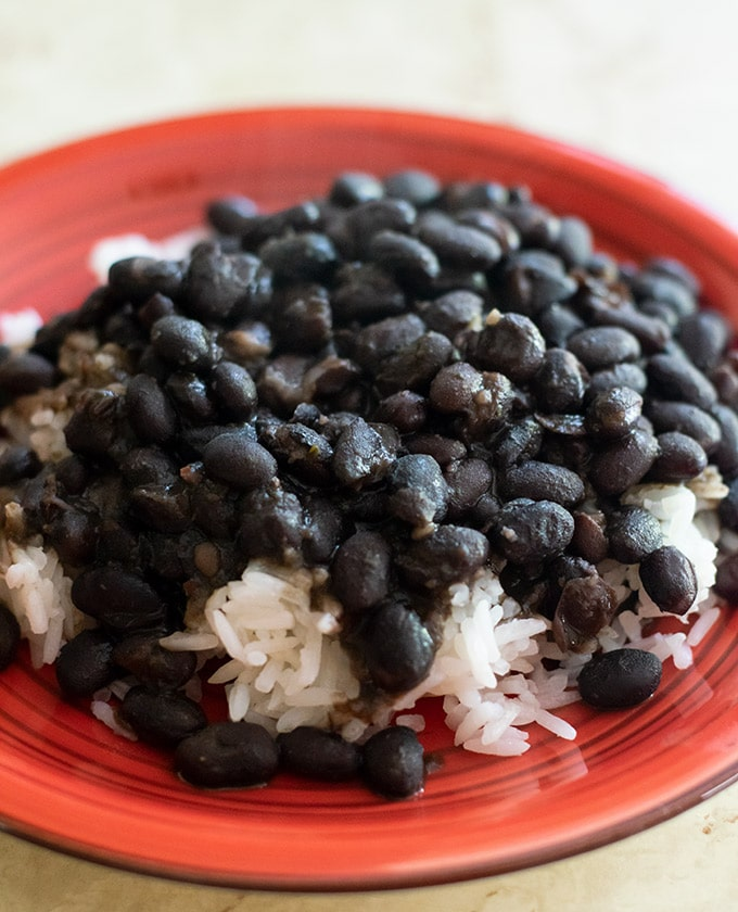 black beans over white rice on a red plate