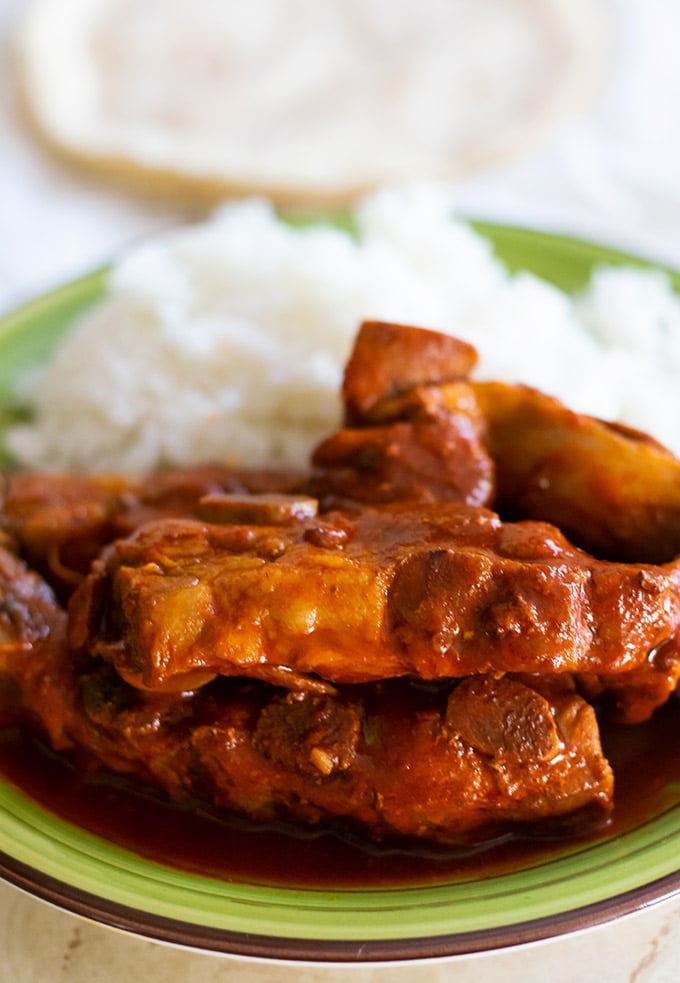 costillas de puerco on a green plate with white rice