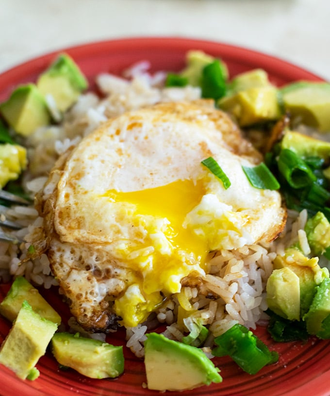 fried egg on rice with green onion and diced avocado
