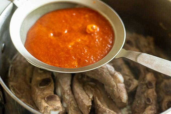straining salsa over ribs