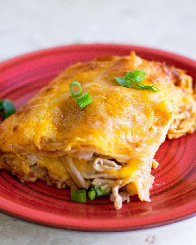 easy chicken enchilada casserole recipe on a red plate