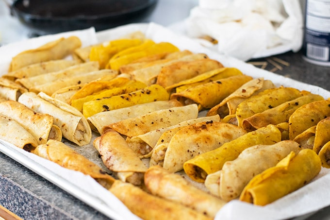 fried taquitos on a baking sheet