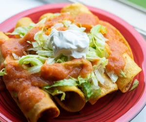 four taquitos garnished with salsa, lettuce and sour cream on a red plate
