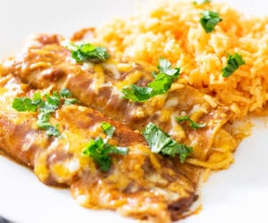 tex mex cheese enchiladas served with rice and garnished with cilantro
