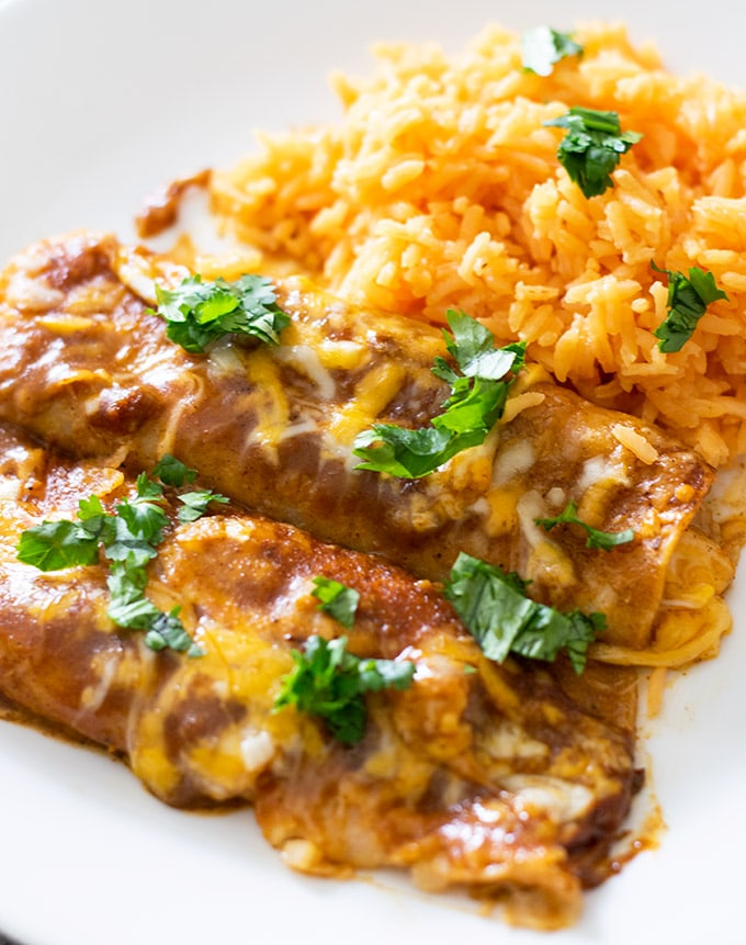 two cheese enchiladas on a white plate garnished with cilantro and rice on the side