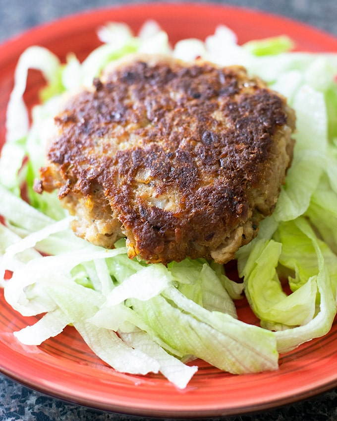tuna patty on a bed of lettuce on a red plate