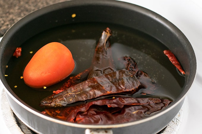dried chilies and a roma tomato in a skillet