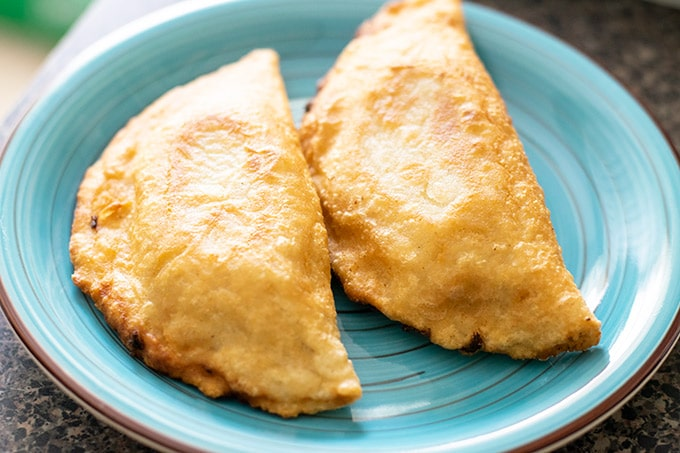 two empanadas on a blue plate