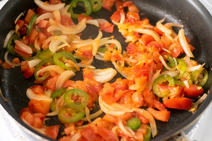 onion, jalapeno and tomato in a skillet