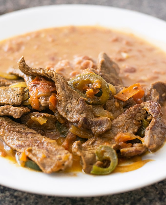 bistec a la mexicana with beans on a white plate