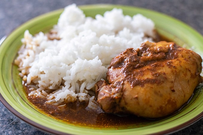 mixiote de pollo with white rice on a green plate
