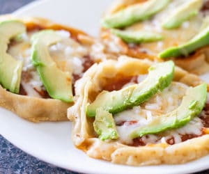 picaditas garnished with diced onion and sliced avocado on a white plate