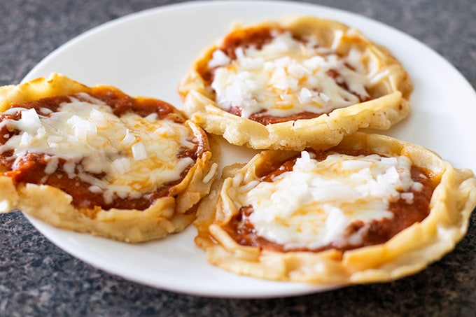 picaditas topped with red salsa, melted cheese and diced onion on a white plate