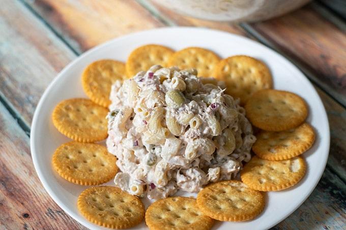 tuna macaroni salad with crackers around it on a white plate