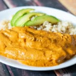 creamy chipotle chicken on a white plate with white rice and sliced avocado