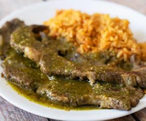 costillas de res en salsa verde with rice on a white plate