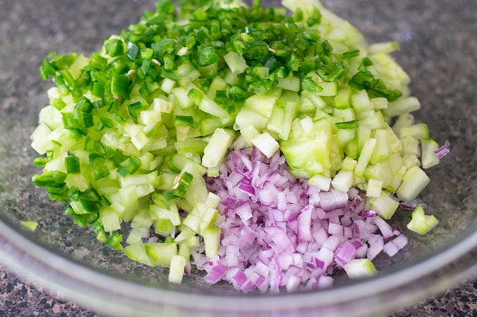 chopped onion, serrano peppers and cucumber in a bowl