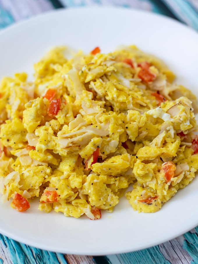 scrambled eggs with turkey on a white plate
