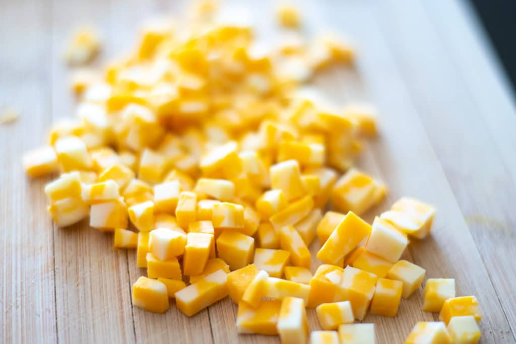 cubed cheese on a cutting board