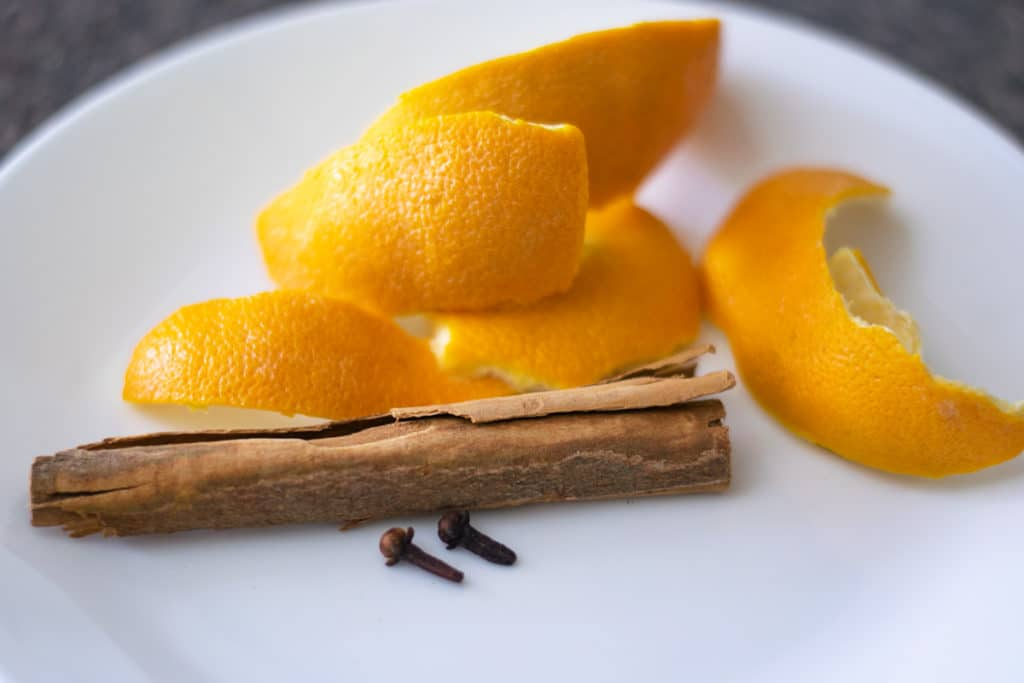 orange peel, cinnamon stick and whole cloves on a white plate