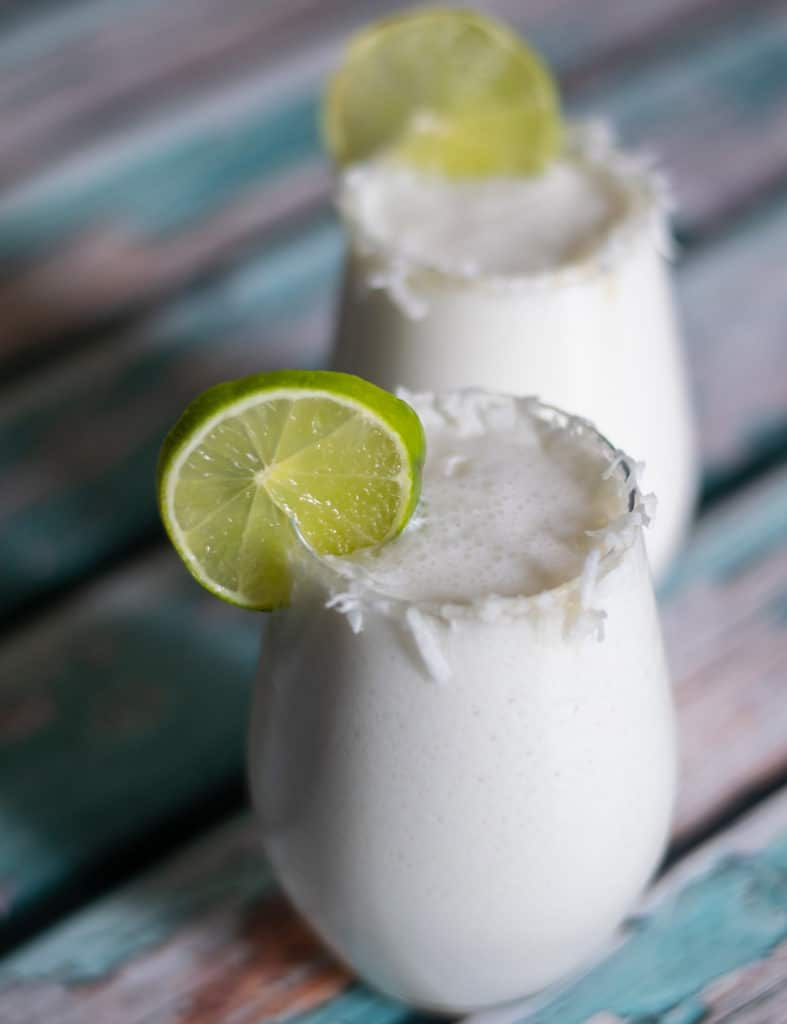 limonada de coco in a glass garnished with coconut flakes and a slice of lime