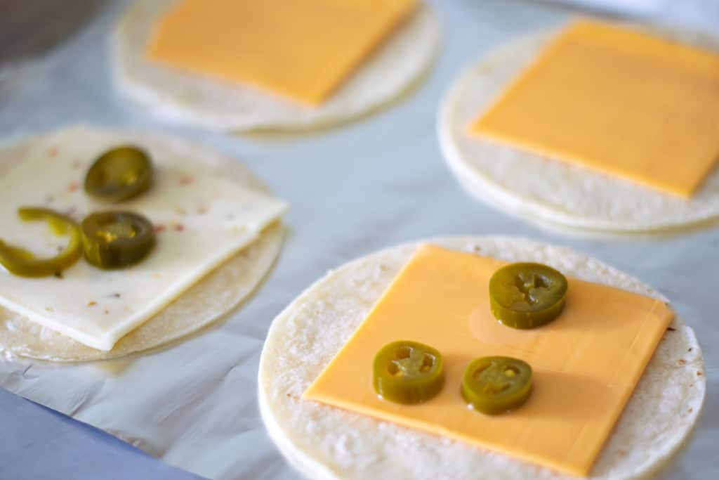 tortillas with cheese slices and jalapenos on a baking sheet