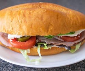 a Mexican ham sandwich on a white plate