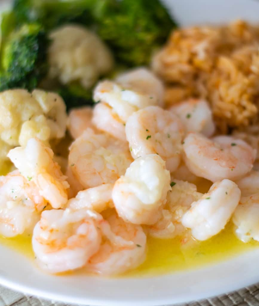 garlic butter shrimp with veggies and rice on a white plate