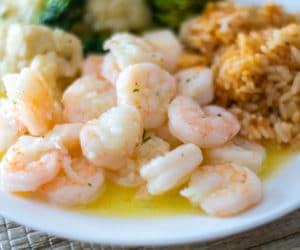 garlic butter shrimp with rice and steamed veggies on a white plate